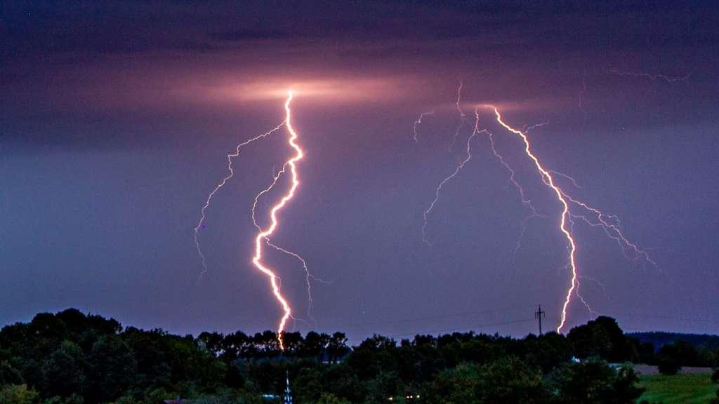 Zwei Blitze gehen über einem erhöhten bewaldeten Gebiet nieder