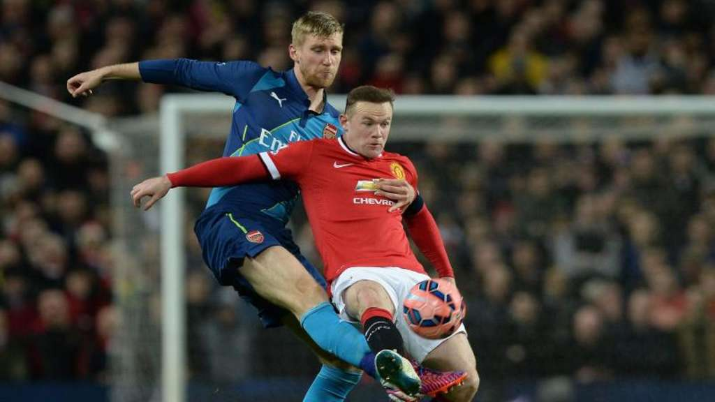 Wayne Rooney (r) wird von Arsenals Per Mertesacker attackiert. Foto: Nigel Roddis